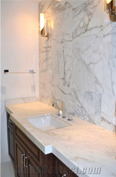 Traditional Bathroom Featuring White Marble Vanity and Calacatta Gold Marble Tile Wall